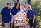 Group of conference attendees standing next to a tiger cutout sign.